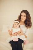Liten flickasammanträde i händerna av en moder fotografering för bildbyråer