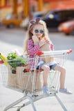 Liten flickasammanträde i shoppingspårvagn arkivfoto