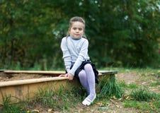 Liten flickasammanträde nära sandlådan Arkivfoto