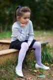 Liten flickasammanträde nära sandlådan Arkivfoton
