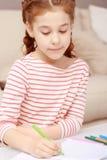 Liten flickasammanträde och teckning arkivbild