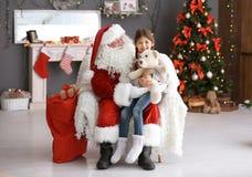 Liten flickasammanträde på autentisk Santa Claus ` sveper inomhus arkivbild