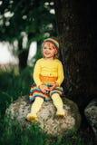 Liten flickasammanträde på den stora stenen Royaltyfria Foton