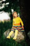 Liten flickasammanträde på den stora stenen Royaltyfri Bild