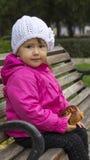 Liten flickasammanträde på en bänk Royaltyfria Foton