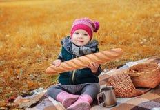 Liten flickasammanträde på en pläd med en bagett Arkivbild