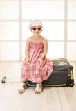 Liten flickasammanträde på en resväska, ordnar till för lopp Royaltyfria Foton