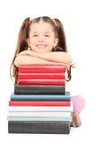 Liten flickasammanträde på golvet bak bunt av böcker royaltyfri fotografi