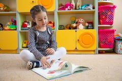 Liten flickasammanträde på golvet och tumma en bok royaltyfria foton