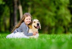 Liten flickasammanträde på gräset med golden retriever Fotografering för Bildbyråer