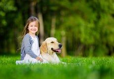 Liten flickasammanträde på gräset med labrador retriever arkivfoto