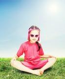 Liten flickasammanträde på gräsmattan och vilar Royaltyfria Bilder