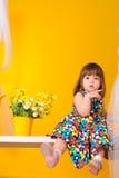 Liten flickasammanträde på gungor med blommor inomhus arkivbilder