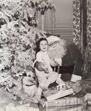 Liten flickasammanträde på jultomten varv under julgranen arkivfoton