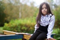 Liten flickasammanträde på lekplatsen Royaltyfri Bild