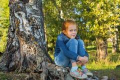 Liten flickasammanträde på rotar av en björk Natur Royaltyfri Fotografi