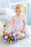 Liten flickasammanträde på säng med buketten av blommor royaltyfria bilder