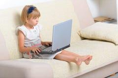 Liten flickasammanträde på soffan med bärbara datorn royaltyfri bild