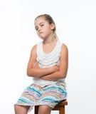 liten flickasammanträde på stol och grinar till kom mischievously royaltyfria bilder