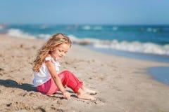 Liten flickasammanträde på stranden i rosa flåsanden Royaltyfria Foton