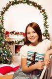 Liten flickasammanträde vid spis med gåva arkivfoto