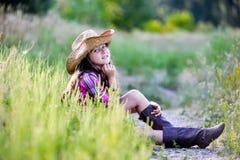 Liten flickasammanträde i ett fält som bär en cowboyhatt Royaltyfri Foto