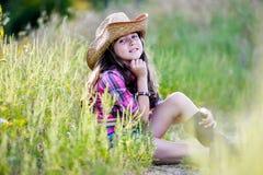 Liten flickasammanträde i ett fält som bär en cowboyhatt Royaltyfri Fotografi