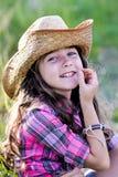 Liten flickasammanträde i ett fält som bär en cowboyhatt Arkivbild