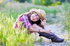 Liten flickasammanträde i ett fält som bär en cowboyhatt Arkivfoto