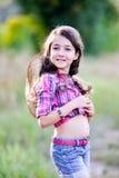 Liten flickasammanträde i ett fält som bär en cowboyhatt Fotografering för Bildbyråer
