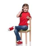 Liten flickasammanträde på en stol och tala vid smartphone Arkivbild