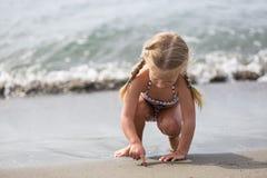 Liten flickasammanträde på stranden Royaltyfria Bilder