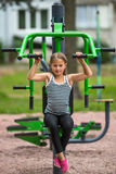 Liten flickasammanträde på övningsutrustning i det offentligt parkerar sport Arkivfoto