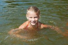 Liten flickasimning i sjön fotografering för bildbyråer