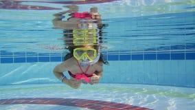 Liten flickasimning under vatten i pölen lager videofilmer