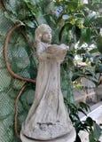 Liten flickaskulptur och på engelska trädgård för gräsplanvinranka Royaltyfria Bilder