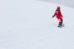 Liten flickasnowboarderen som ner rider på, skidar lutningen i franska fjällängar Arkivbilder