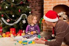 Liten flickaspelrum med farsan nära julgran Royaltyfri Foto