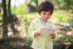 Liten flickaspelrum med tableten Arkivbilder