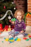 Liten flickaspelrum nära julgran Fotografering för Bildbyråer