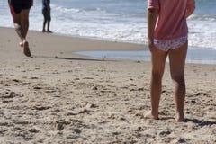 Liten flickaspring längs havet på en sandig strand royaltyfri foto
