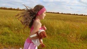 Liten flickaspring på äng med solnedgång tonat flickaungen kör längs den lantliga vägultrarapidvideoen flicka little lager videofilmer