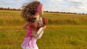 Liten flickaspring på äng med solnedgång tonat flickaungen kör längs den lantliga vägultrarapidvideoen flicka little stock video