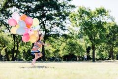 Liten flickaspring som är snabb med en grupp av färgrika ballonger royaltyfria bilder