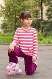 Liten flickaståendesommar utomhus på rullarna Arkivbild