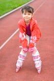 Liten flickaståendesommar utomhus på rullarna Fotografering för Bildbyråer
