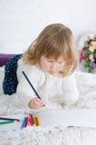 Liten flickateckning i säng royaltyfria foton