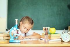 Liten flickateckning på skolan över den gröna skolasvart tavla arkivfoto