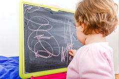 Liten flickateckning på svart tavla Fotografering för Bildbyråer