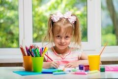 Liten flickateckningsmålarfärger och färgpennor till ett rum med ett fönster royaltyfri foto